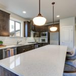 New kitchen boasts dark wood cabinets white backsplash subway tile and over sized island with white and grey quartz counter illuminated by pendant lights. We are a Silestone quartz countertop dealer.