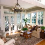 Furnished sun room with large windows and glass doors